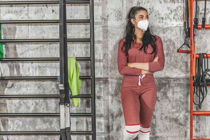 Portrait of sporty woman wearing surgical face mask at gym during pandemic - coronavirus