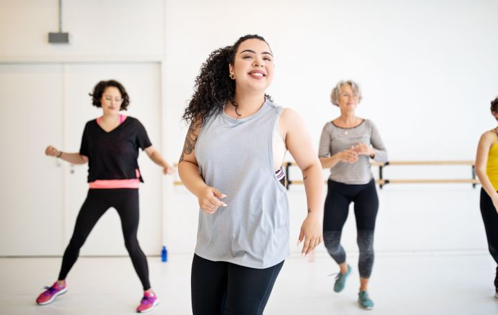 Young woman learning dance moves in fitness class. Multi-ethnic women dancing in studio.
