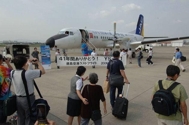 YS-11のラストフライトに向かう搭乗客。「41年間ありがとう!」と横断幕が掲げられた=2006年9月30日、徳島空港。朝日新聞社撮影