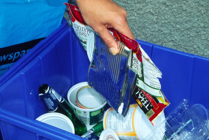 File photo of a person adding items into a recycling blue box.