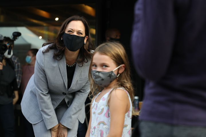 United States Senator and Democratic Vice Presidential nominee Kamala Harris greet and takes a picture with a child after greeting patrons of Trophy Brewing and Pizza at a planned campaign stop in Raleigh, North Carolina.