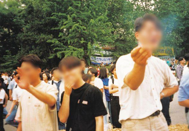 이화여대 총학생회 카메라에 잡힌 고대생이다. 사진을 찍는 현장의 분위기가 어땠을지 전해진다. 두 남학생은 담배를 피우며 의기양양한 표정을 짓고 있다. 20년 뒤인 지금까지 악습의 한...