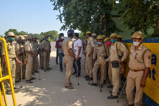 Police personnel stand guard at a road near the premises of the relatives of the 19-year-old woman on...