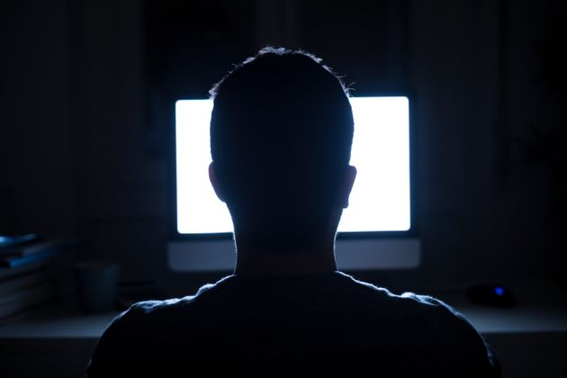 Silhouette of man's head in front of computer monitor light at