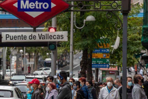 Personas con mascarilla junto a la estación de Metro de Puente de Vallecas el sábado 19...