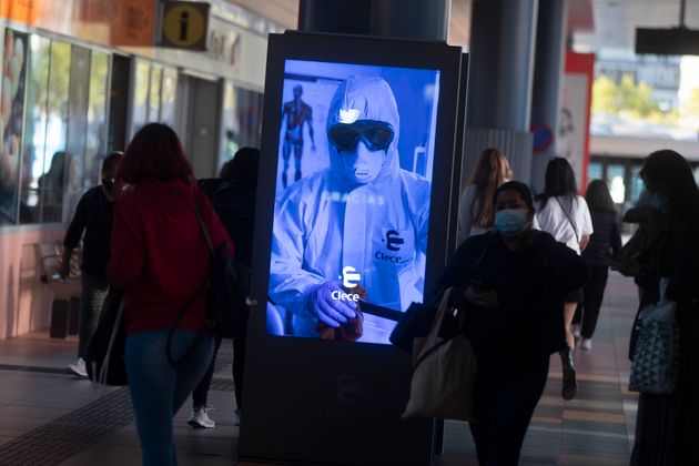 People pass by a poster thanking medical workers at a bus station in Madrid, Spain, Wednesday, Oct. 7,...