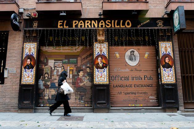 Una mujer con mascarilla pasa por delante de un restaurante