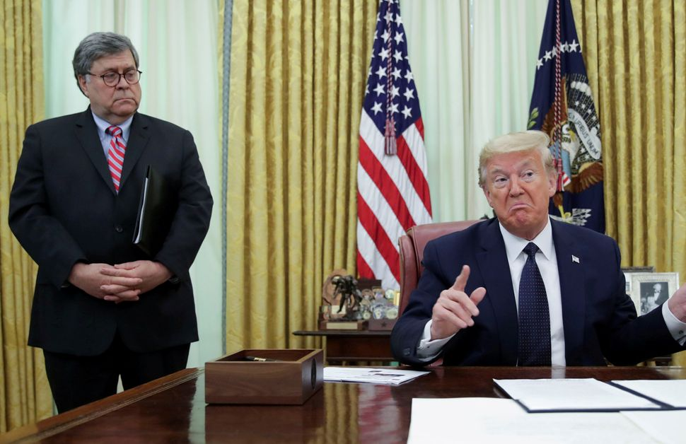 President Donald Trump speaks to reporters in the Oval Office in May as Attorney General William Barr listens.