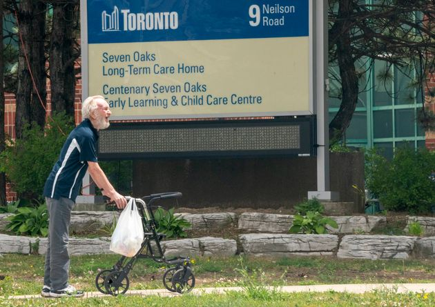 A man takes a walk outside the Seven Oaks Long-Term Care Home in Toronto on June 25,