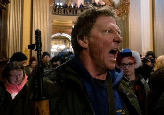 知事が出した外出禁止令の延長投票に抗議し、ミシガン州都にある議事堂で州警察に向かって叫ぶ人物(2020年4月30日)
