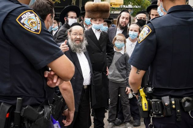Members of the Orthodox Jewish community speak with NYPD officers on a street corner in the Borough Park...