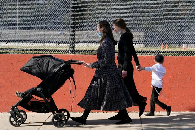 Two women walk with children during the Jewish holiday of Sukkot in the Borough Park neighborhood of...