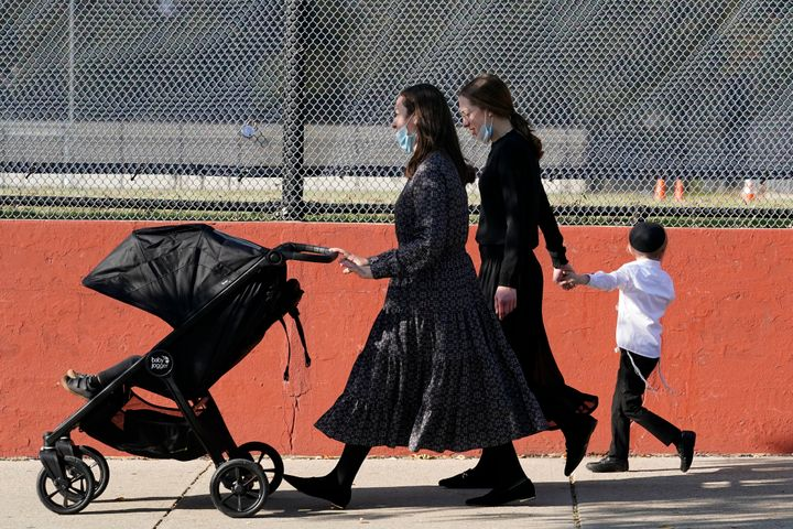 Two women walk with children during the Jewish holiday of Sukkot in the Borough Park neighborhood of New York.