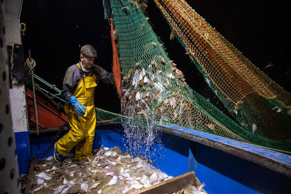 Fishermen work in the English Channel, off the coast of