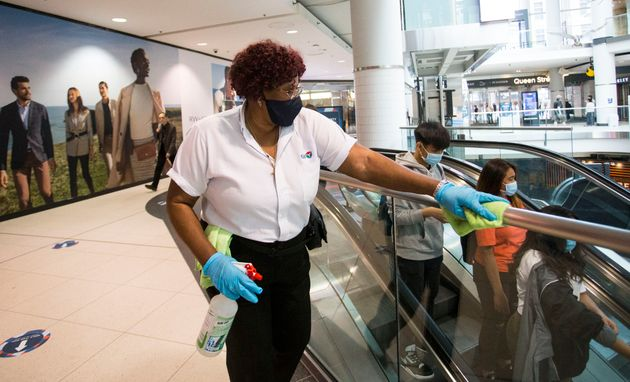 A worker wearing a face mask cleans a handrail at CF Toronto Eaton Center in Toronto, June 24, 2020....