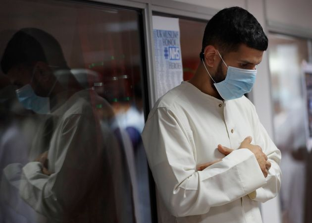 A Muslim man wears a face mask to protect against coronavirus as Muslims gather to pray at Minhaj-ul-Quran...