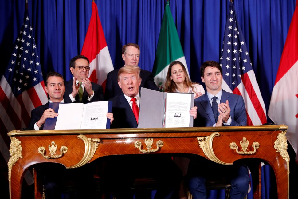 President Donald Trump signs a revised North American trade agreement alongside Canadian Prime Minister Justin Trudeau and th
