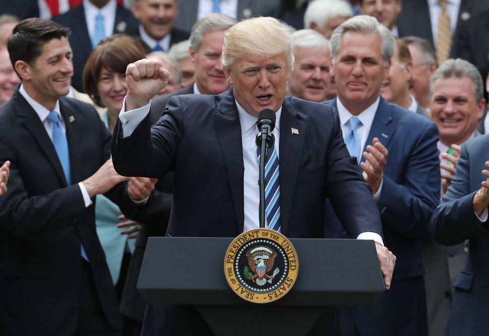 Trump celebrates the House's vote to repeal the Affordable Care Act with then-House Speaker Paul Ryan (Wis.), left. The presi