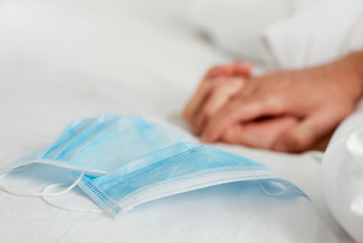 A pair of surgical masks on a bed with two people gripping their hands in the background.