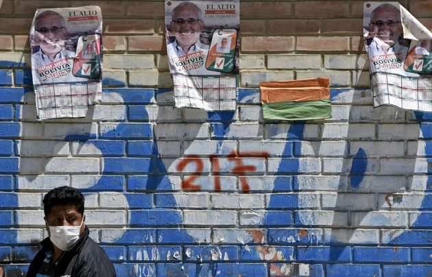 A man walks past a graffiti with political propaganda of former Bolivian President Evo Morales, and posters...