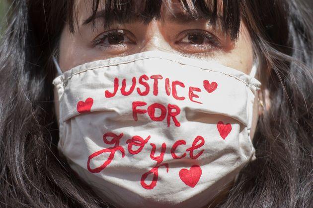 Une femme porte un masque à une manifestation intitulée «Justice pour Joyce»...