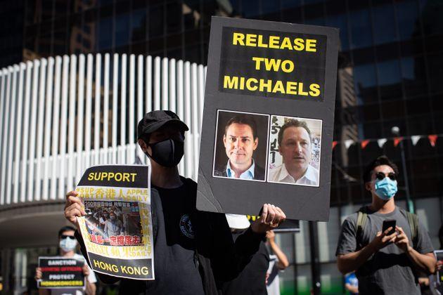 Un manifestant tient une pancarte sur laquelle figurent les photos de Michael Kovrig et Michael Spavor...