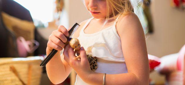 Caucasian girl combing doll's