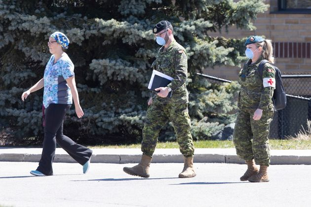 A staff member escorts members of the Canadian Armed Forces in to a long term care home, in Pickering,...
