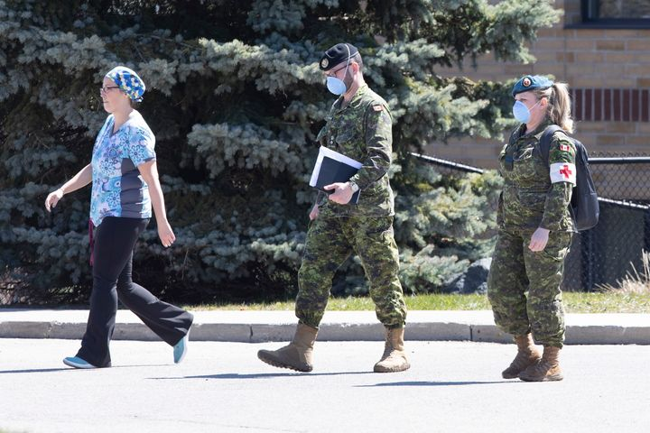 A staff member escorts members of the Canadian Armed Forces in to a long term care home, in Pickering, Ont. on April 25, 2020.