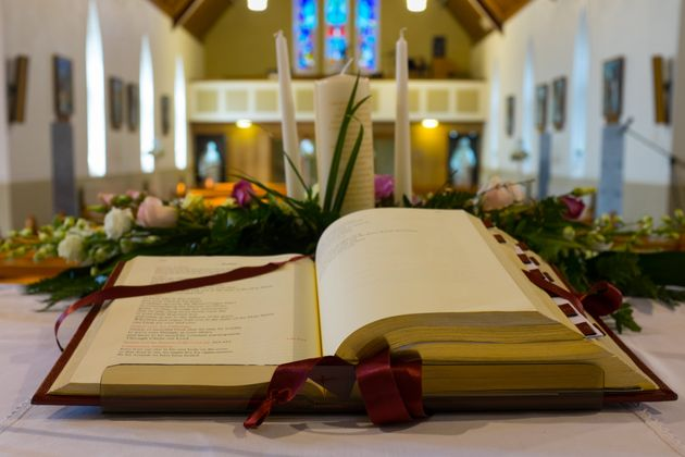 Open Bible and wedding flowers on the altar in catholic church. Shallow