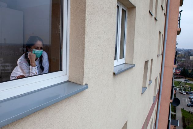 A 40-year-old woman wearing a protective mask is looking out of the window. Home quarantine for 14 days...