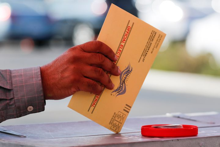 An election worker places a mail-in ballot into an election box at a drive-through drop-off location at the Registrar of Vote
