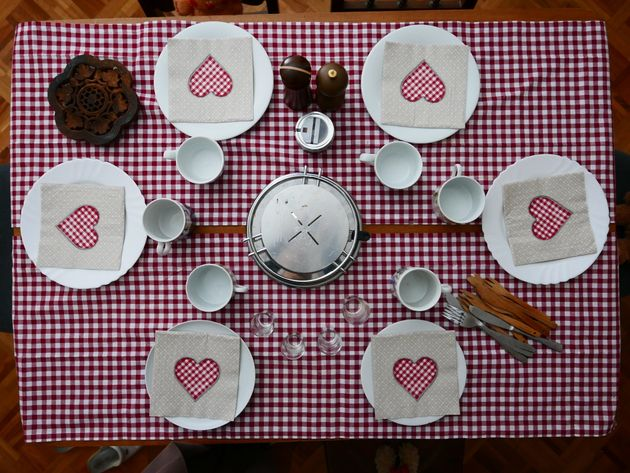 Party table set with tiled tablecloth and heart napkins for 6 guests on a special