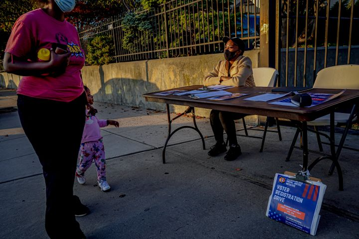 Laurae Caruth, a volunteer with Christian Cultural Center Social Justice Initiative's voter registration drive, sits at a table where she registers voters, Friday, Sept. 18, 2020, in the Brooklyn borough of New York.