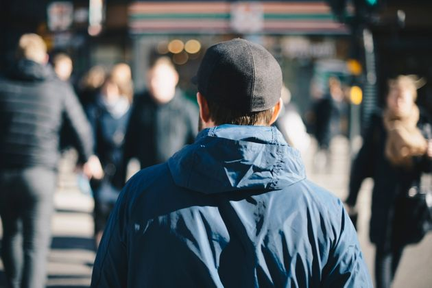 Rear view of man wearing blue jacket on city street during