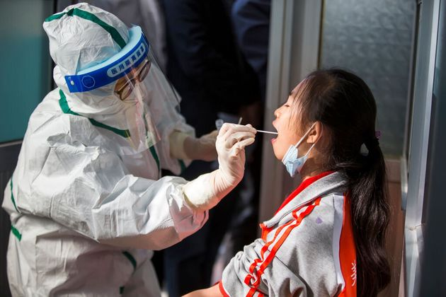A child receives a coronavirus test Tuesday in Binzhou, China, after visiting the city of Qingdao after...