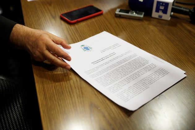 Cardinal Angelo Becciu shows a document as he talks to journalists during press conference in Rome, Friday,...