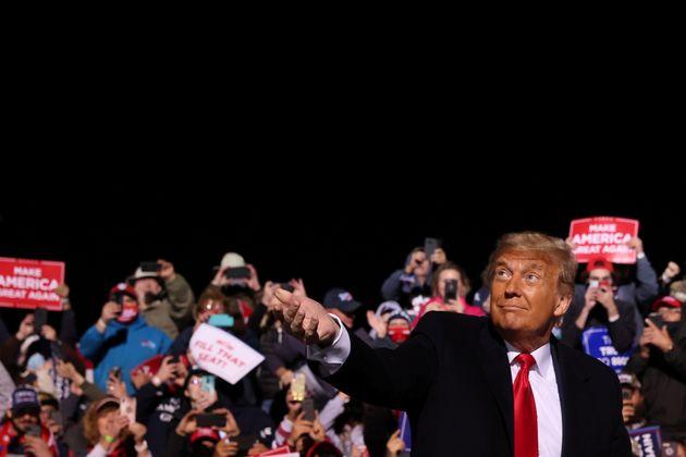 선거 유세장에 도착한 도널드 트럼프 미국 대통령이 청중들에게 마스크를 던져주고 있다.존스타운, 펜실베이니아주. 2020년