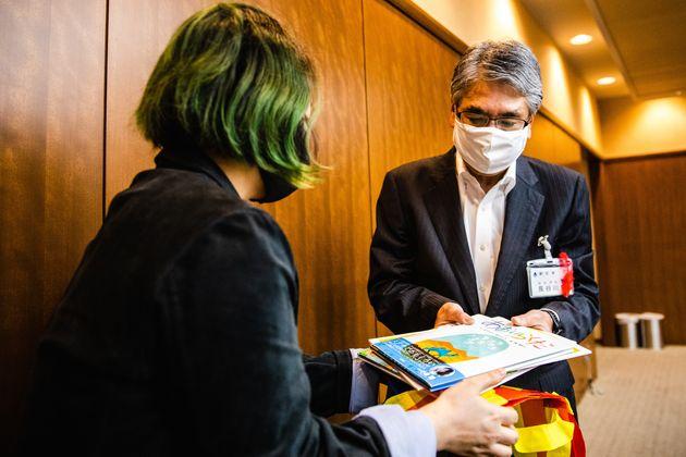 『あおいらくだ』などの絵本を長谷川副区長に渡す長村さん