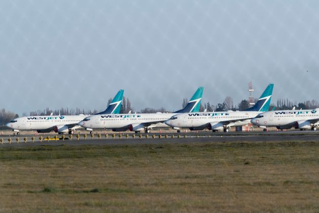 WestJet planes sit grounded at Vancouver International Airport in Richmond, B.C., April 9, 2020. The...