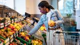 Female shopping grocery in organic shop. African woman with face mask buying fresh fruits from produce aisle in supermarket.