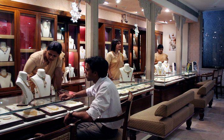 Un hombre busca joyas en una sala de exposiciones de Tanishq en Kolkata, India. & Nbsp;
