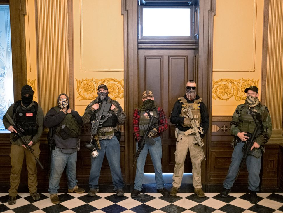 A Michigan militia group stands in front of the governor's office April 30 after protesters occupied the state Capitol in Lan