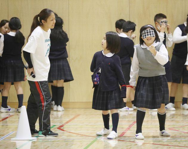 開幕半年前のイベントで、小学生に特別授業をする東京パラリンピック陸上女子走り幅跳び代表の高田千明選手(左)と伴走などを務める大森盛一さん=2020年2月25日、東京都江東区