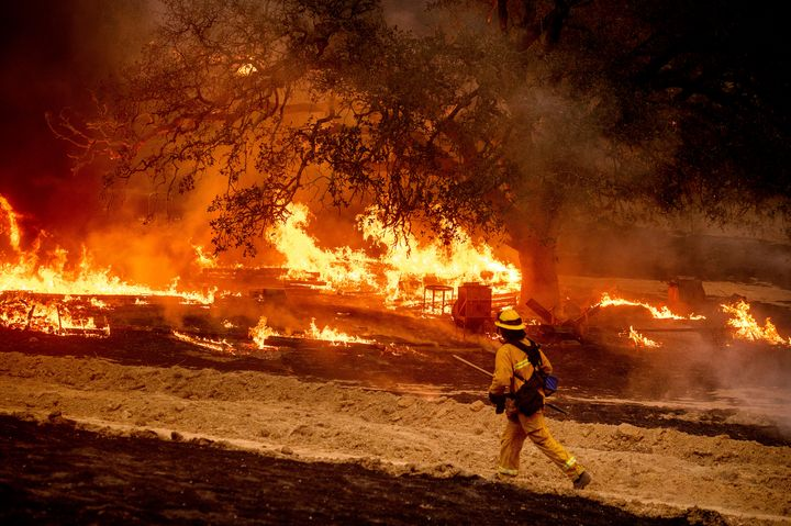 A firefighter passes flames while battling the Glass Fire in a Calistoga, Calif., vineyard on Oct. 1, 2020.
