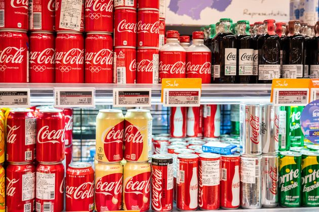 Una estantería llena de latas de Coca-Cola en un