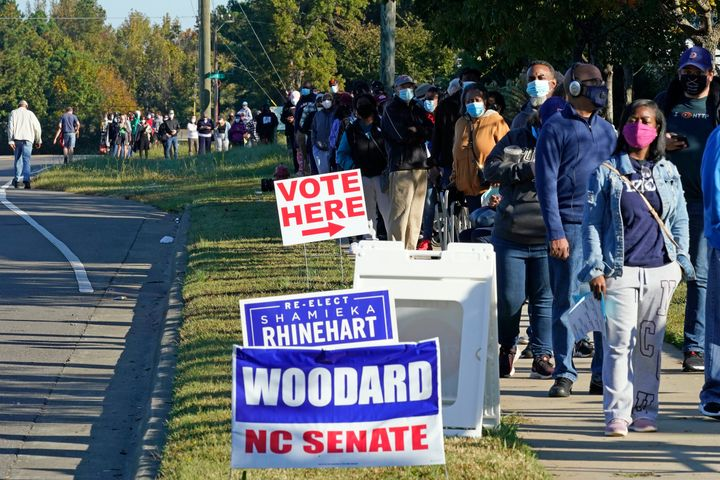 Early voters form a long line while waiting to cast their ballots at the South Regional Library polling location in Durham, North Carolina, on Oct. 15, 2020. Some waited almost three hours to vote.