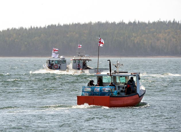 Members of the Potlotek First Nation, head out into St. Peters Bay from the wharf in St. Peter's, N.S....