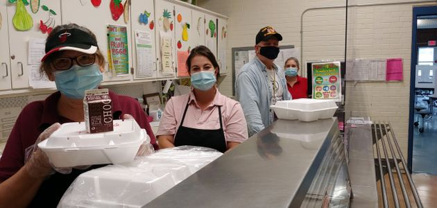 Ann Pulisz (right) works in a school cafeteria in Wallingford, Connecticut. The cafeteria staff is shorthanded...