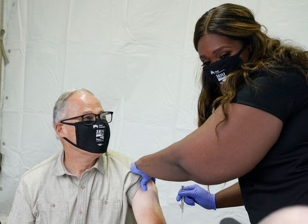 Washington Gov. Jay Inslee, left, gets a flu shot from Cenetra Pickens, a nurse with Kaiser Permanente,...